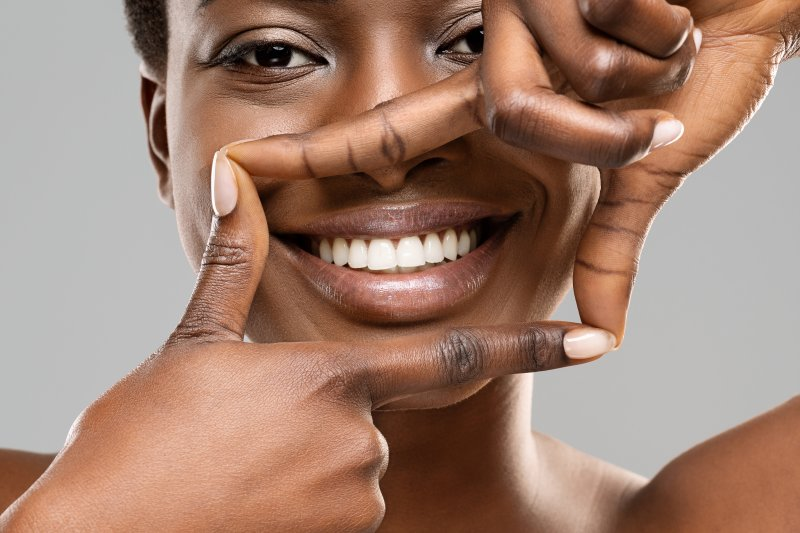 Smiling woman framing her teeth with her fingers