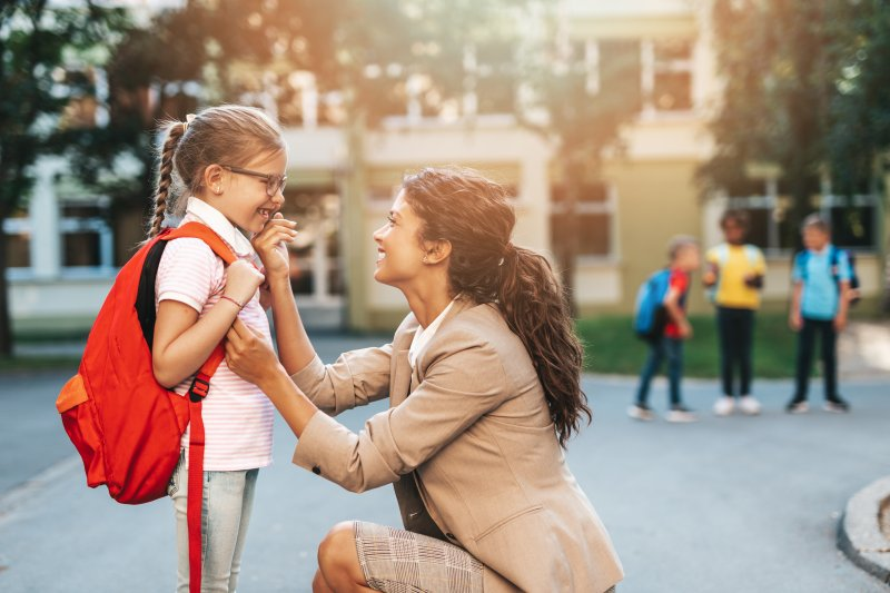 Mom and daughter smiling on first day of school